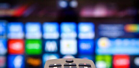 Controle remoto com tela de tv atrás