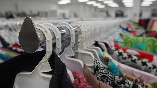 Várias roupas em cabides de uma loja
