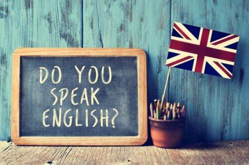 Pequena lousa escrito: Do you speak english? e ao lado, um vaso com lápis e bandeira do Reino Unido