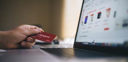 Pessoa segurando cartão de crédito para pagar contas e boletos