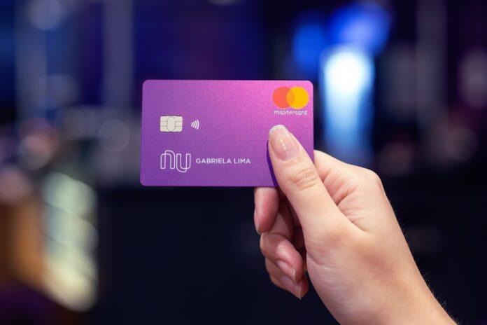 Mulher segurando cartão de crédito do Nubank