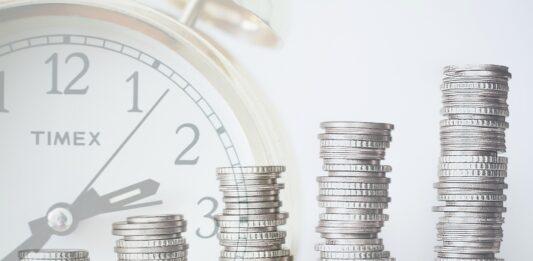 montagem de um relógio no fundo com cinco fileiras de moedas
