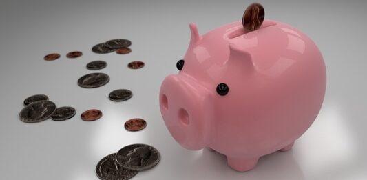 Cofre de porquinho com algumas moedas espalhadas na mesa