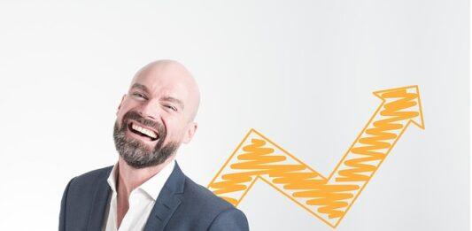 Homem careca de blazer rindo e um gráfico de seta atrás