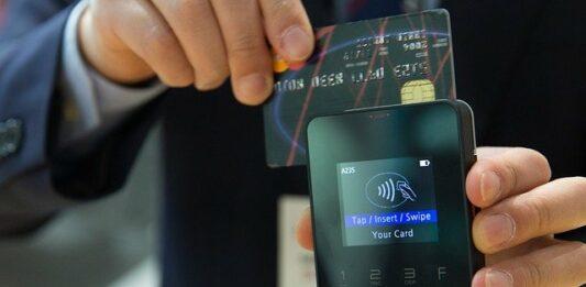 Homem passando cartão de crédito em uma máquina de cartão