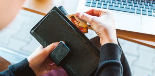 Mulher retirando cartão de crédito de uma carteira grande preta