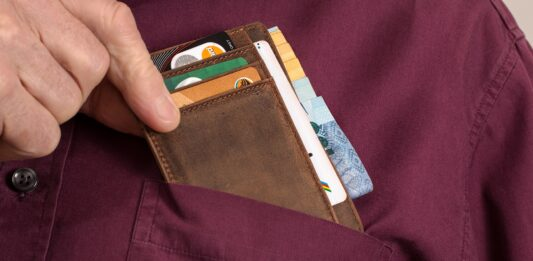 Homem colocando carteira com vários cartões de crédito no bolso da camisa