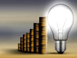 lâmpada acesa com moedas empilhadas atrás