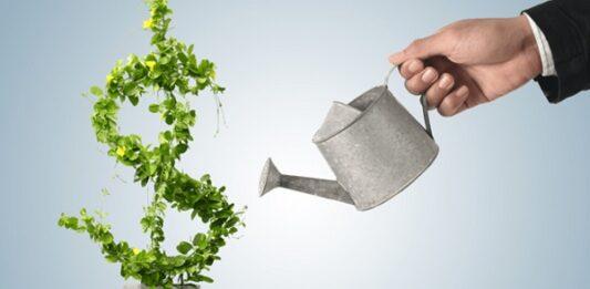 Homem regando uma planta com formato de cifrão