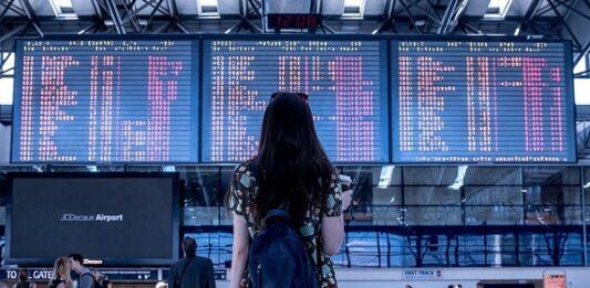 Mulher de costas usando mochila, observando horários de voo em um aeroporto