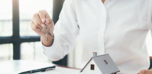 Homem segurando chaves em uma mesa com casa em miniatura e plancheta