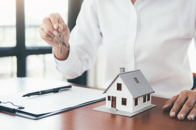 Pessoa segurando chaves na mão com uma maquete de uma casa em cima da mesa