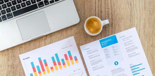 Mesa de trabalho com notebook, papéis com gráficos e xícara de café