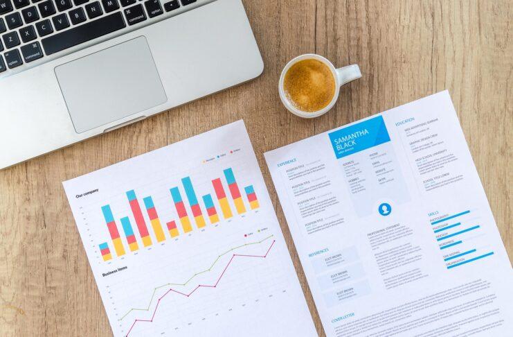 notebook com uma xícara de café e papéis com gráficos