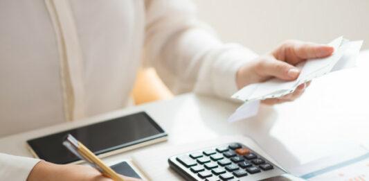 Mulher fazendo anotações utilizando calculadora