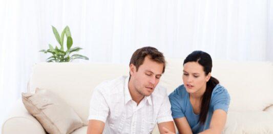 casal sentado no sofa analisando contas no SPC