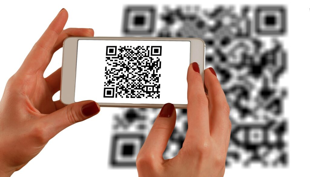Imagem com uma pessoa apontando o celular para o QR Code para ilustrar o texto sobre PIX