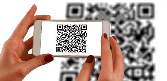 Mulher aproximando celular de QR Code