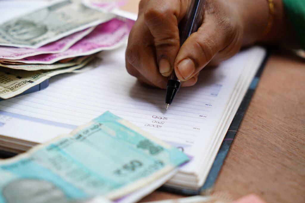 Homem fazendo controle de gastos com várias notas de dinheiro