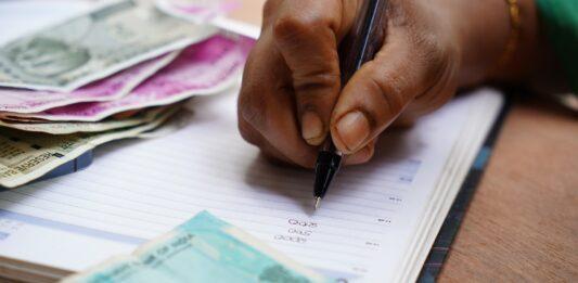 Pessoa fazendo cálculos em um caderno com várias notas de dinheiro
