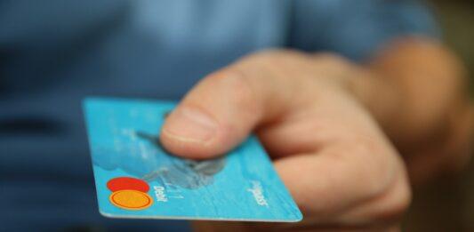 Homem mostrando um cartão de crédito com cashback