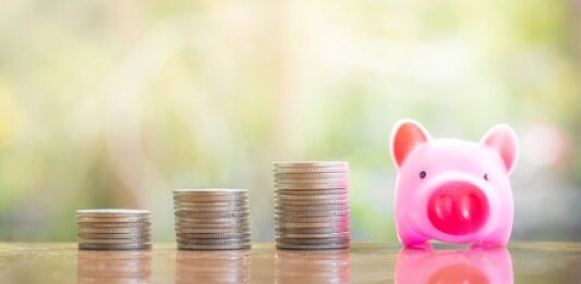 3 moedas empilhadas em forma de gráfico ao lado de um cofre de porquinho