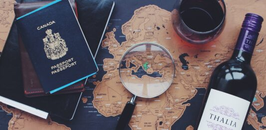 Mapa mundi com lupa, passaportes, garrafa de vinho e câmera fotográfica