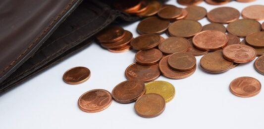 carteira com moedas espalhadas