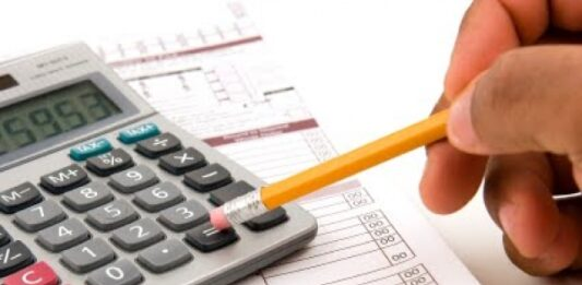 Pessoa usando calculadora com lápis em cima de vários papéis