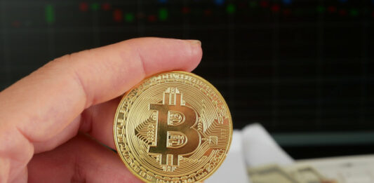Pessoa segurando um Bitcoin com pacote de dinheiro ao fundo