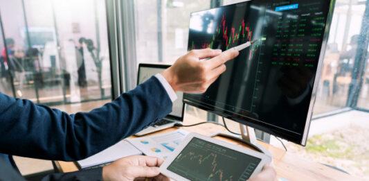 Homem analisando gráficos de investimentos em uma tela de computador e outro olhando gráficos em um tablet
