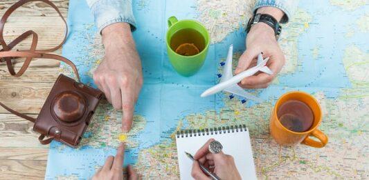 Duas pessoas analisando mapa mundi tomando chá e fazendo anotações