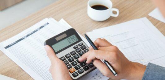 Mulher usando calculadora em uma mesa de trabalho
