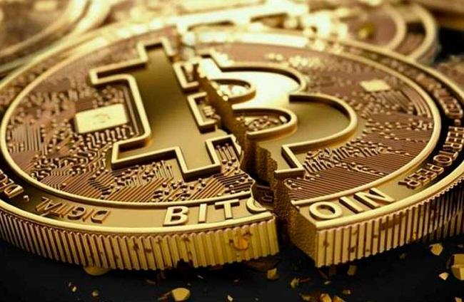 moeda dourada com o símbolo do bitcoin rachada ao meio