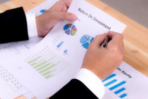 Inimigos do investidor: homem de terno escrevendo em um papel com gráficos