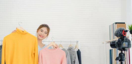 Mulher segurando dois cabides com blusas em uma loja de roupa