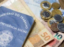 Carteira de trabalho em cima de notas de dinheiro e moedas