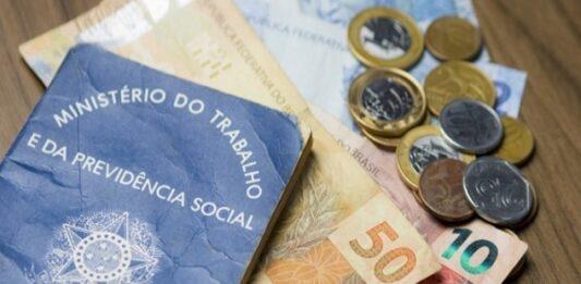 Carteira de trabalho em cima de notas de reais e moedas