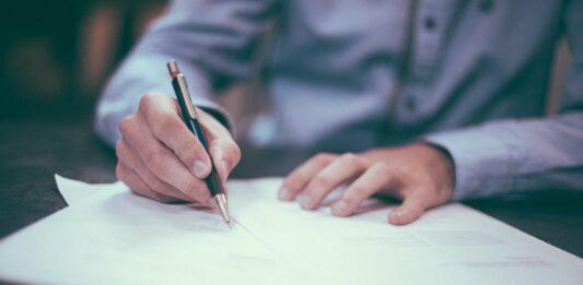 um homem de roupa social com caneta na mão assinando contrato