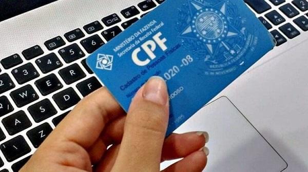Mulher segurando o cartão do cpf em cima do teclado do notebook