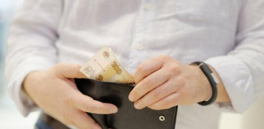 Homem de roupa social com carteira na mão mexendo em dinheiro