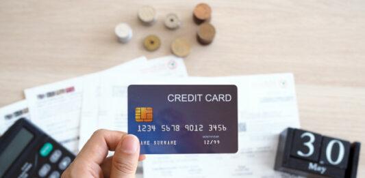Homem segurando um cartão de crédito em uma mesa com papéis, calculadora e calendário