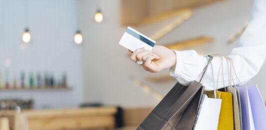 Mulher segurando cartão de crédito e carregando algumas sacolas de compras
