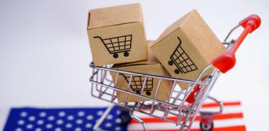 Carrinho de compras carregando 3 pequenas caixas de papelão em cima de uma bandeira dos EUA
