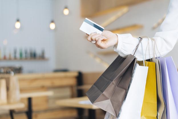 Mulher em uma loja com cartão na mão e sacolas coloridas no braço