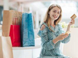 Mulher sorridente ao lado de pacotes de compras, segurando um cartão de crédito e celular