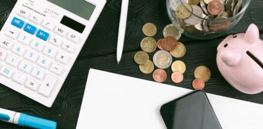 Calculadora, moedas, cofre de porquinho, canetas, papel em branco e celular em uma mesa
