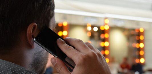 Homem falando no celular em um lugar público