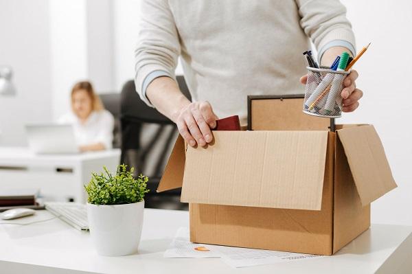 Pessoa guardando seus pertences do trabalho após pedido de demissão