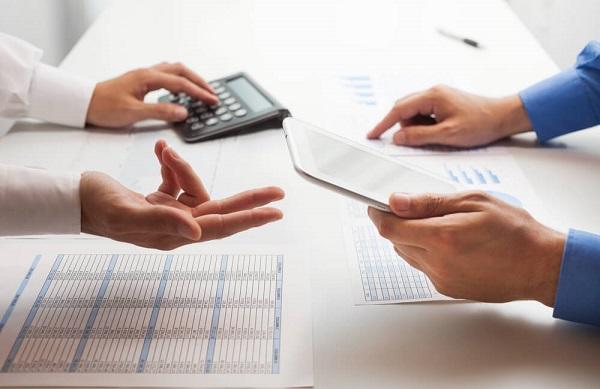 Duas pessoas usando calculadora, tablet e analisando papéis com informações financeiras